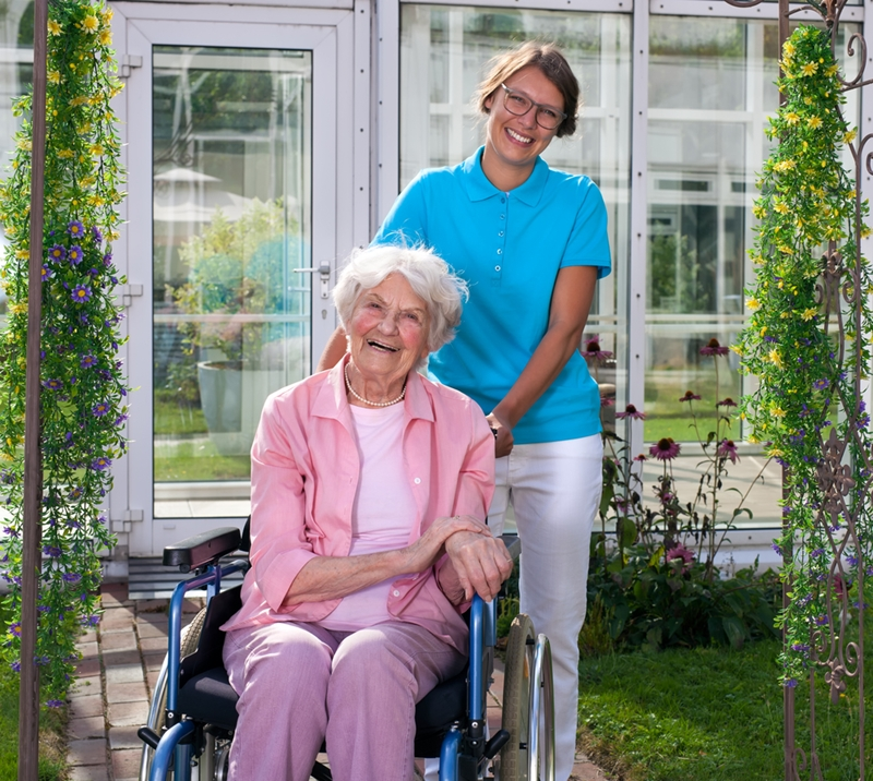 A women pushes a senior in a wheelchair in her backyard.